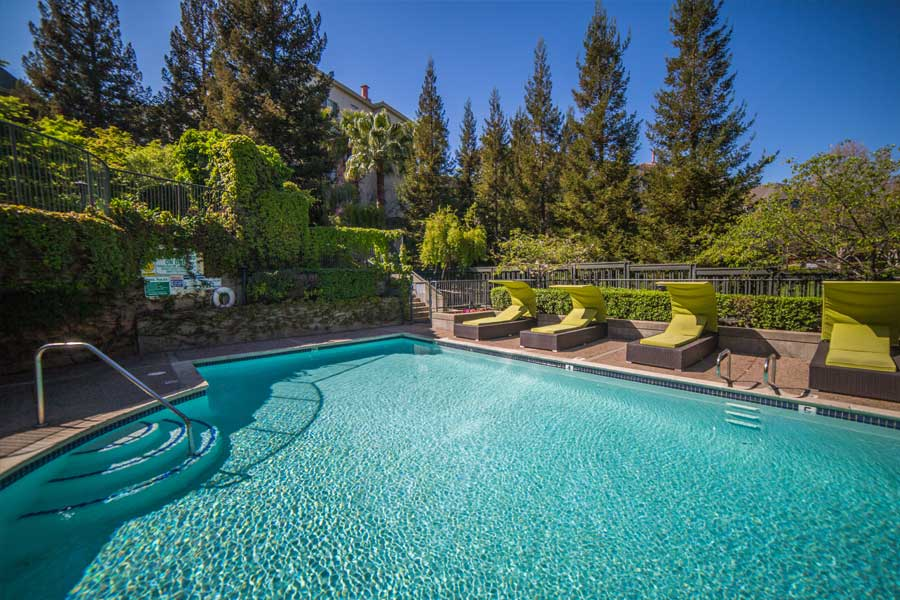 Sparkling pool with natural stone walls and lounge chairs at our Walnut Creek, CA apartments.